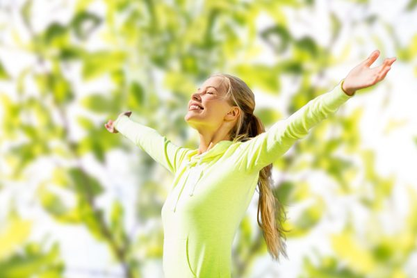 happy woman in sport clothes raising hands